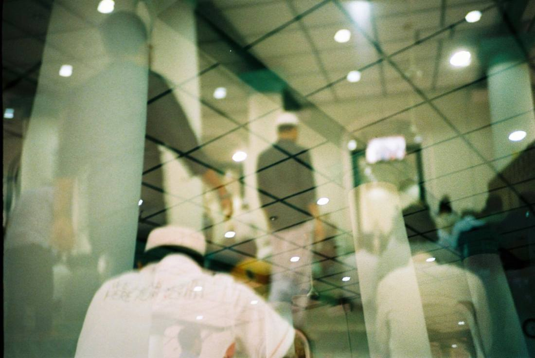 double exposure image of men in mosque
